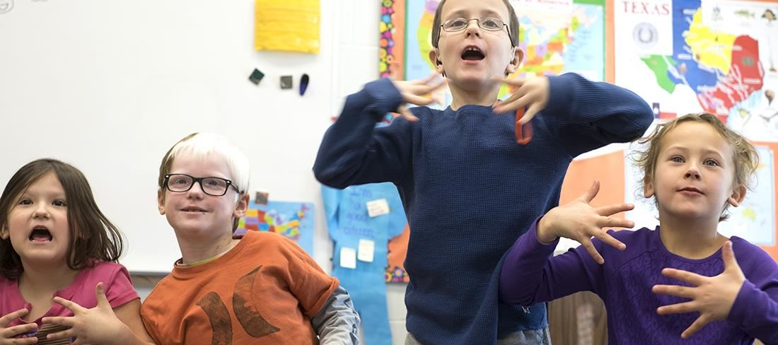 Four young students using sign language in class.