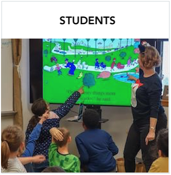 Students - A teacher pointing to a large screen with students sitting on the floor facing the screen. Some are pointing to the screen