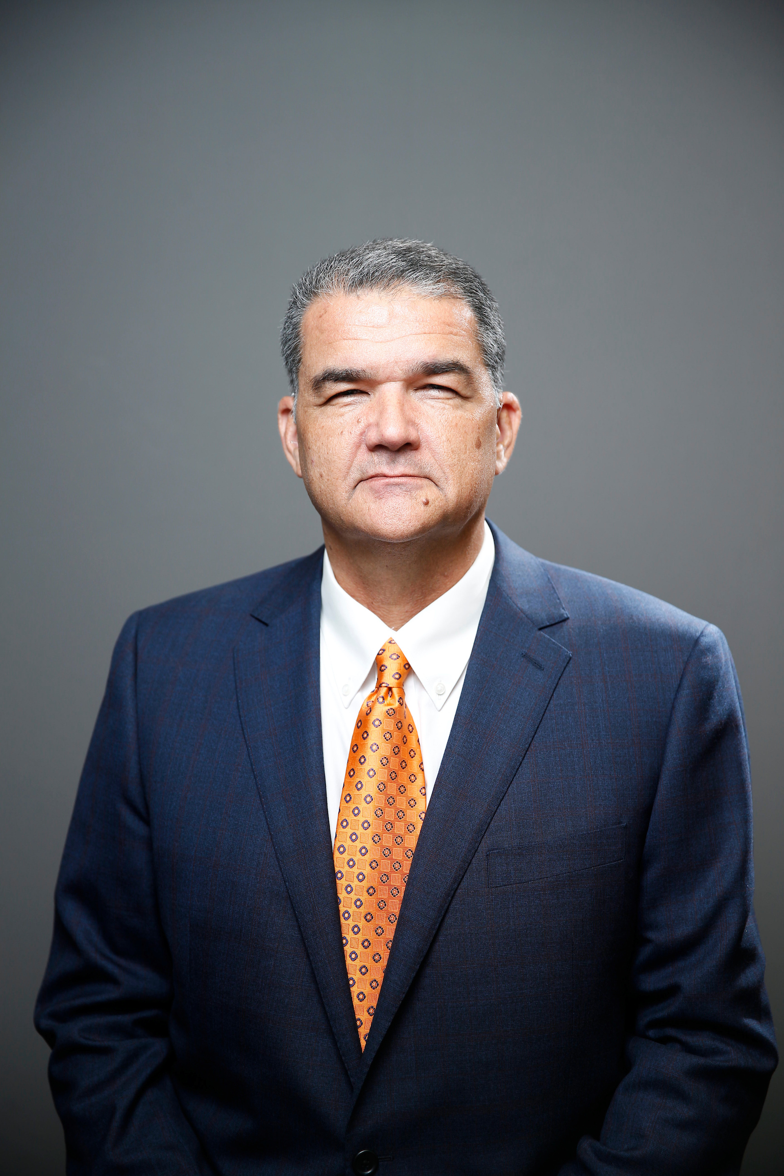 Dr. Saladin - hispanic male wearing suit with orange tie.