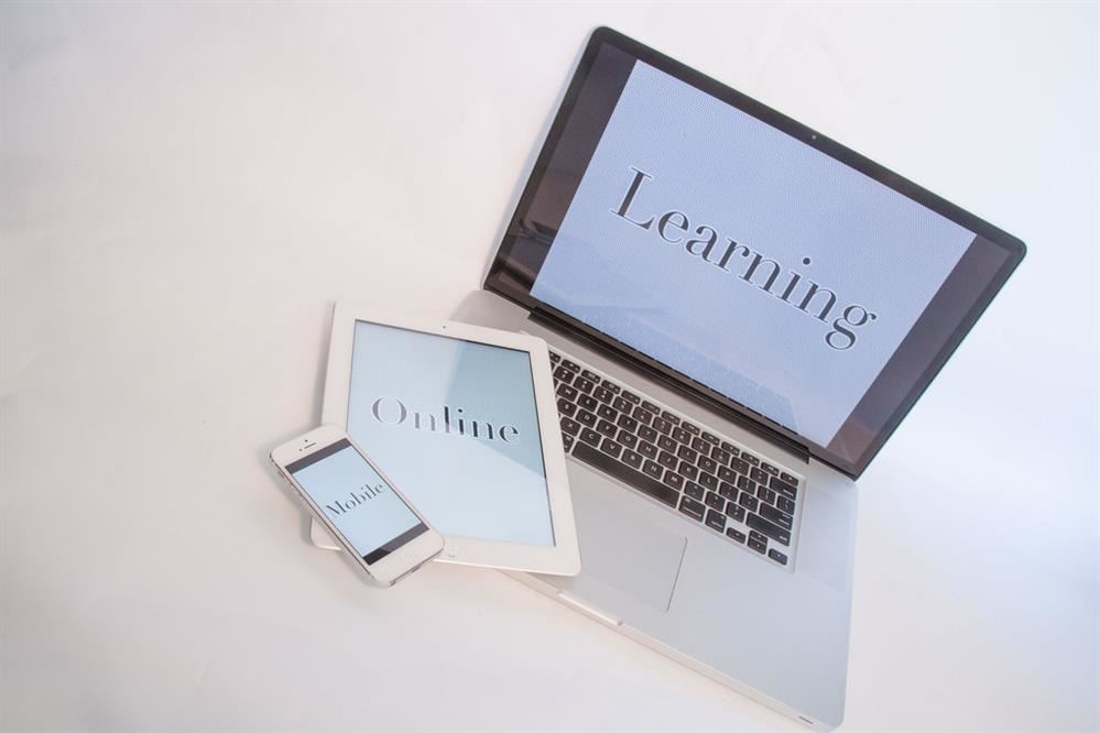 Laptop, ipad and iphone that says Learning Online Mobile