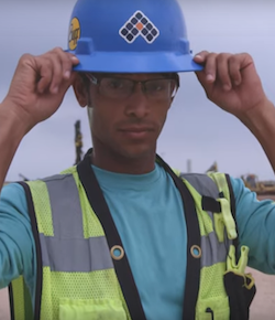 Aaron Diaz - light skinned male with glasses wearing blue hard hat and yellow vest.
