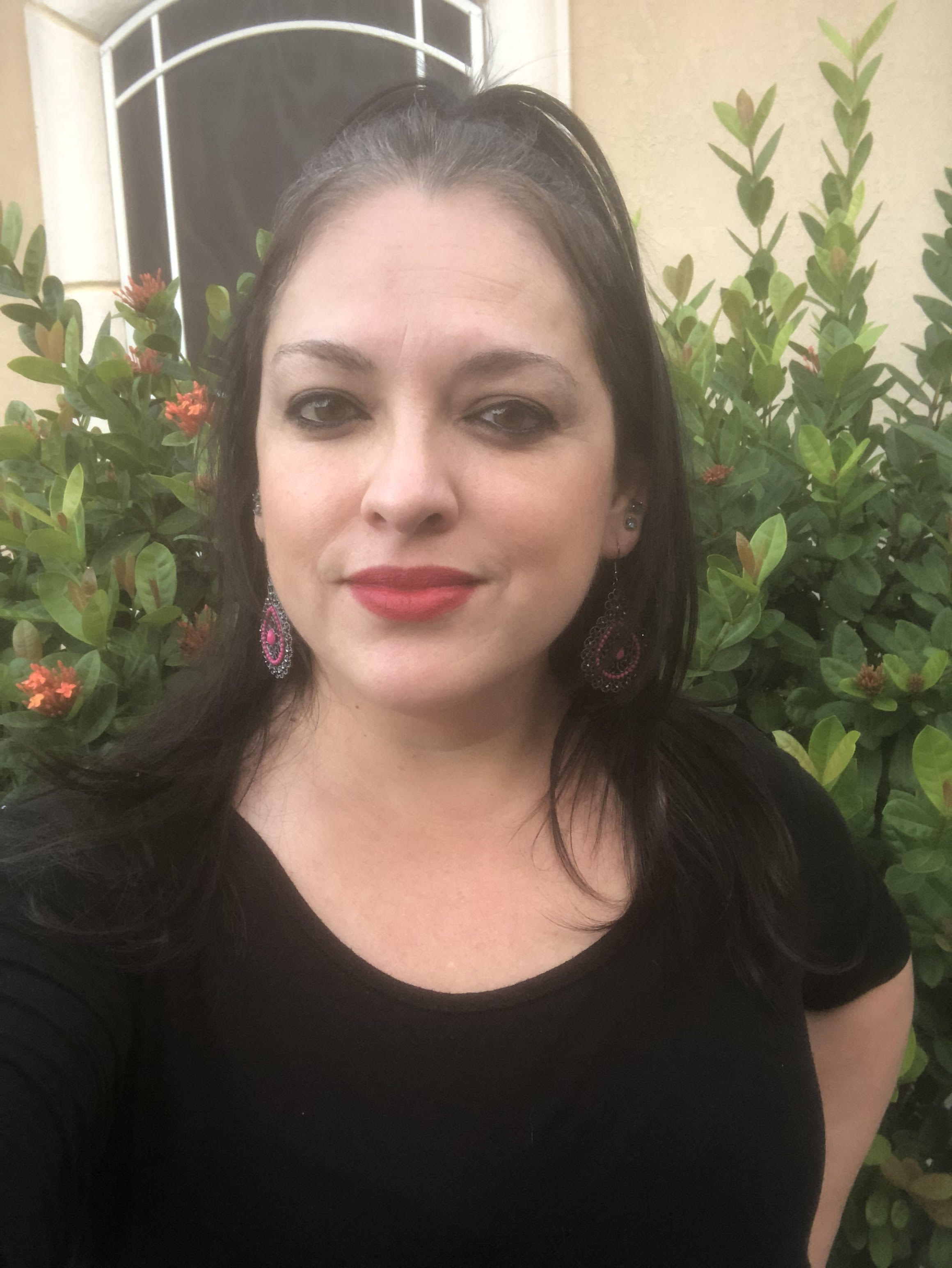 Linda Lugo - Hispanic female with red lipstick, black shirt and greenery with few pink flowers in background.